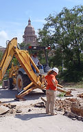 Archaeologist monitoring backhoe trench excavations along Block 4 in downtown Austin.