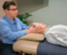 Doctor provides an osteopathic treatment to an elderly patient on a table