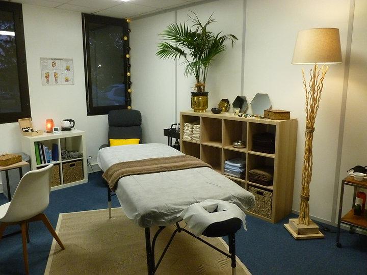 Cabinet de massage avec sa table au centre, des étagéres à serviettes, un fauteuil, un coin bureau, un tapis beige sur une moquette bleu, une plante verte , des miroirs et autres bibelots, le tout éclairé par un joli luminaire donne cette ambiance à cocon blanc massage tassin