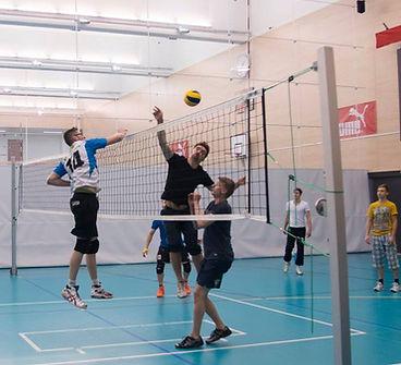 Henkilöitä pelaamassa lentopalloa