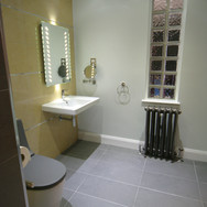 A modern yellow and grey tiled level access wet room