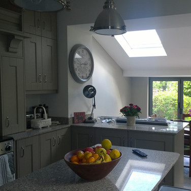 A traditional khaki and stone grey hand-painted kitchen extension