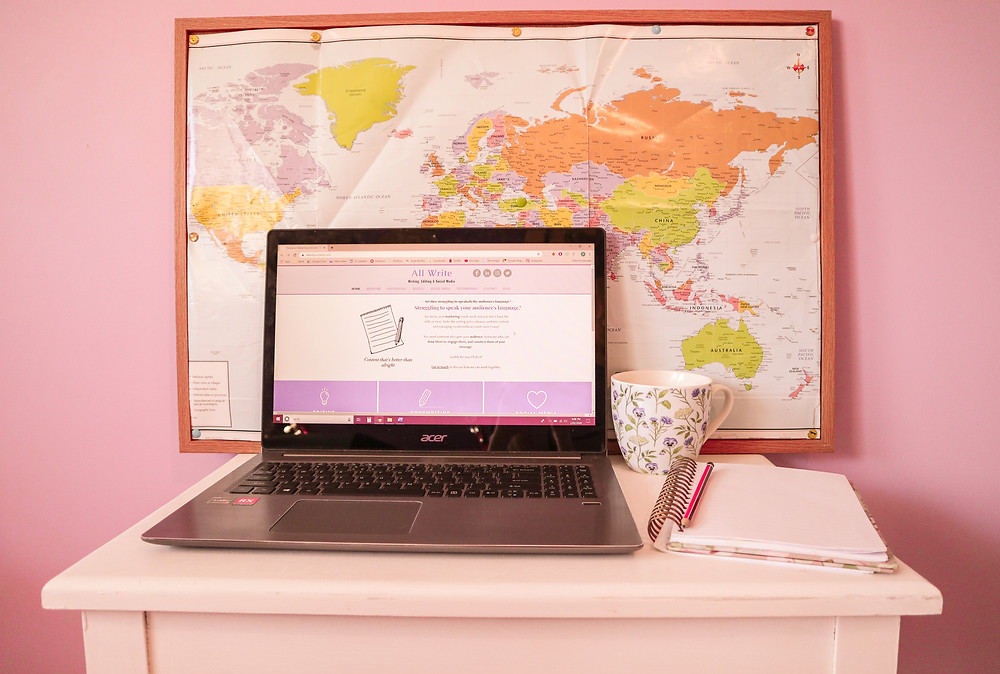 Desk with laptop, notebook, world map and mug. All Write website displayed on laptop.