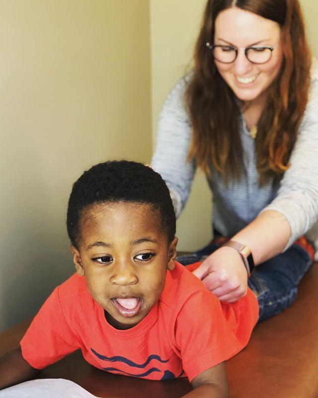 Dr. Annie adjusting a wiggly toddler.