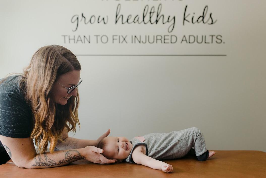 Dr. Annie adjusting a super cute baby.