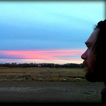 Man's profile looking at the sun setting over the horizon