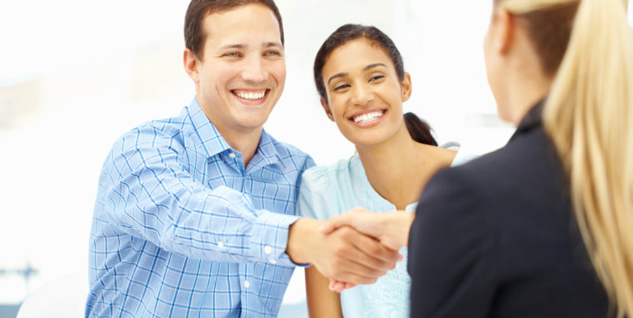 Happy couple shaking hands with business woman