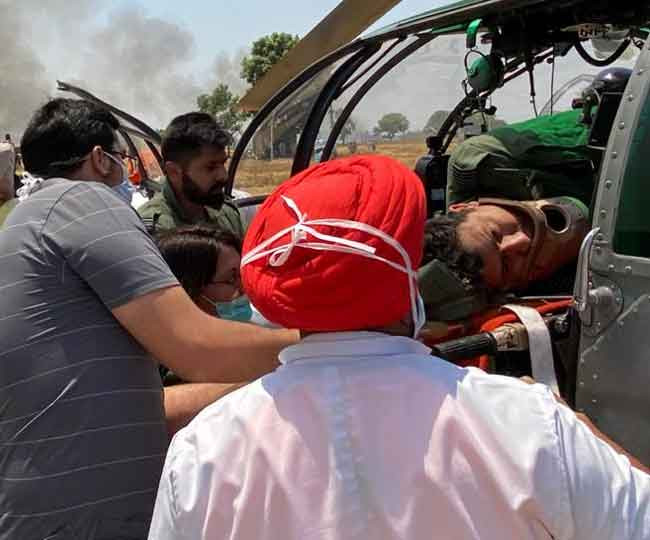 पायलट को दूसरे हेलिकॉप्टर में ले जाते हुए