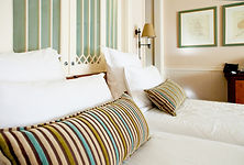 A hotel bedroom with stripey pillows
