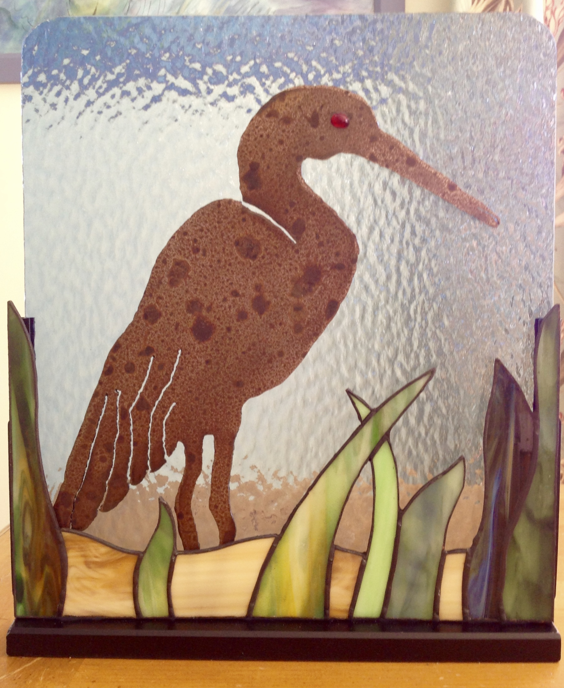 Steel heron on stained glass