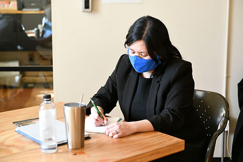 A Filipina woman wearing all black except for a blue mask doing desk work.