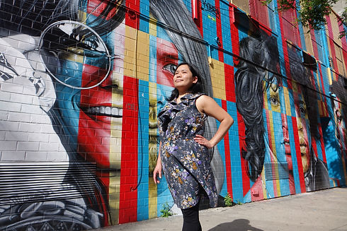 Giselle with her eyes closed and the sun on her face in front of a colourful mural.