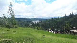 The Edmonton River Valley on a bright day with fluffy clouds and green grass and trees.