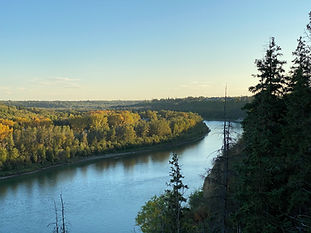 The river valley at sunset, with the sun shining on trees on the left side of the river.