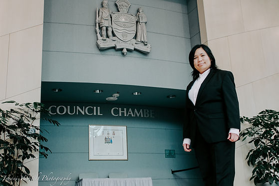 A Filipina woman with short hair posing in front of the Council Chambers in Edmonton's City Hall.