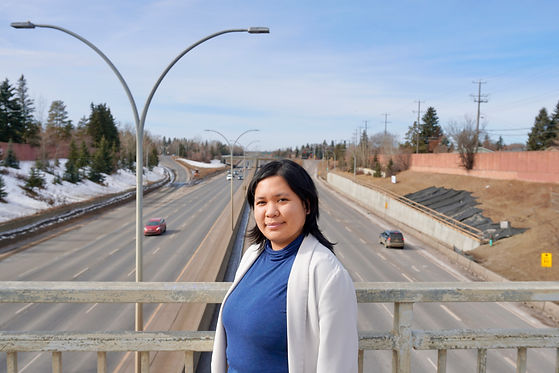 A Filipina woman wearing a blue turtleneck and white blazer, posing in front of Whitemud in West YEG