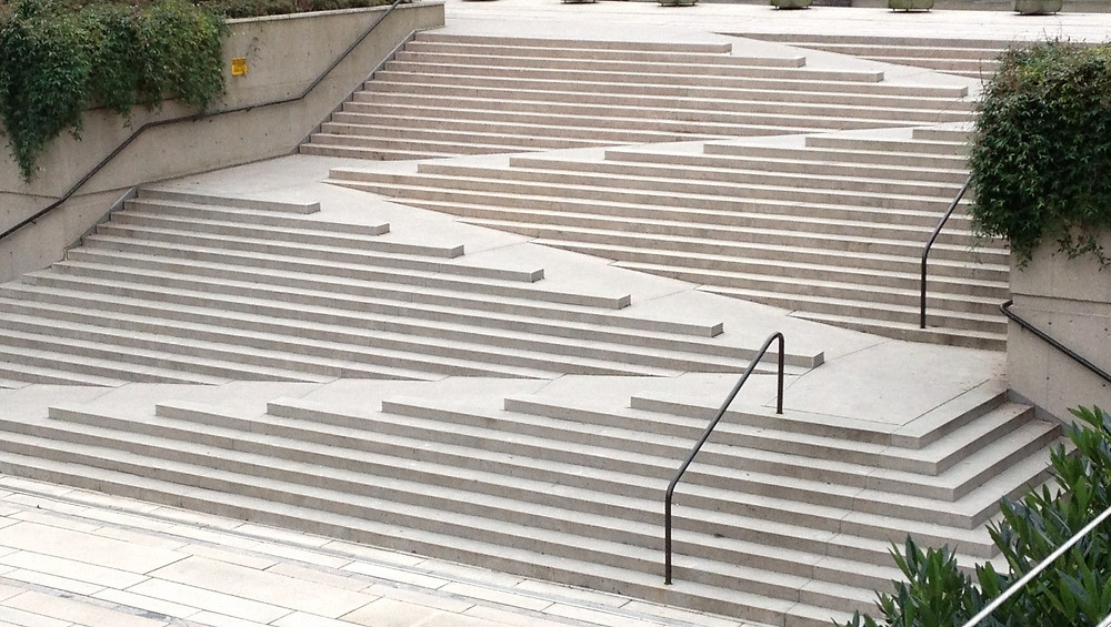 An architectural design that weaves together stairs and a ramp in a zig-zag pattern.