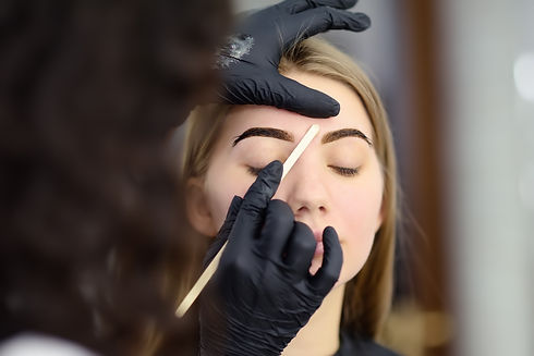 Cosmetologist making eyebrows design. At