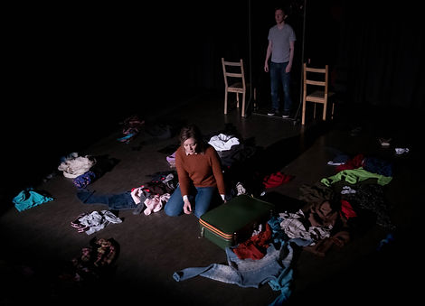 From the play Loneliness by Greg Nanni: an actor sits on the floor surrounded by piles of clothes and a suitcase, another actor stands behind her between two chairs, watching