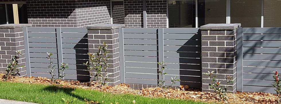 Painted treated pine slats between brick