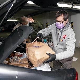 Zastępca burmistrza Włodzimierz Piątkowski pakuje do bagażnika auta paczki pomocowe przygotowane przez Urząd Dzielnicy dla seniorów i osób na izolacji.