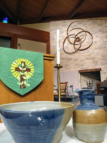 Baptismal decanter and bowl, lectern, Christ candle and Trinity sculpture on church altar