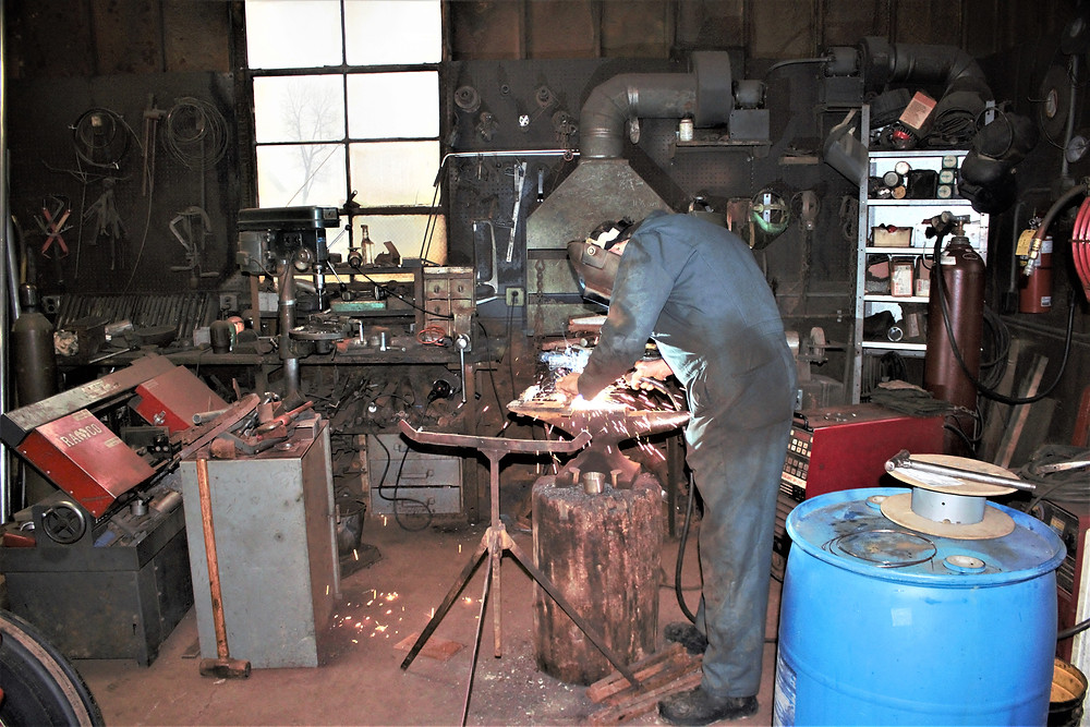 Time spent with the welder is well spent. The anvil, fused to the stump with railroad spikes his palette. Sparks fly off the canvas.
