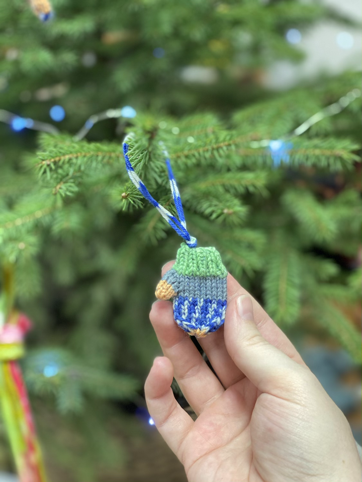 A pale hand holds a tiny hand knit mitten ornament as it hangs on a holiday tree