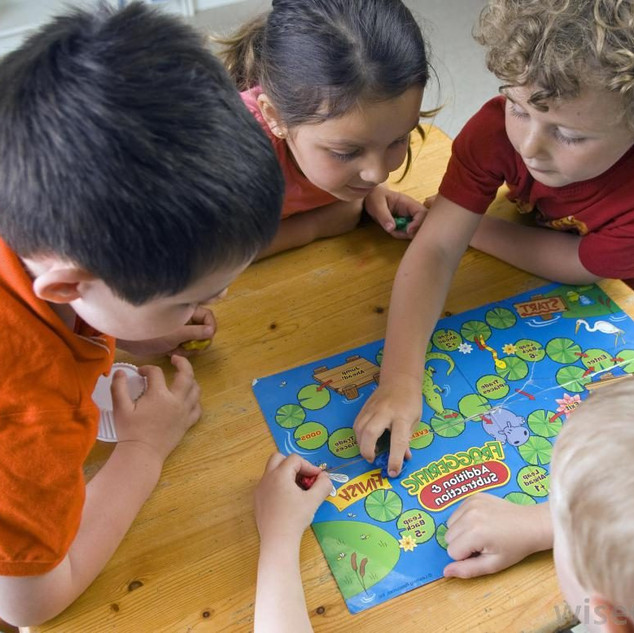 children-playing-board-game-on-table.jpg