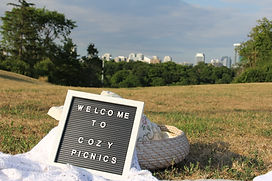 "A felt board with words that say ""welcome to cozy picnics"" in a park"