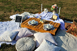 Picnic spread in a park with wooden crate. Two plates on top of the crate, a blanket spread with cushions everywhere.