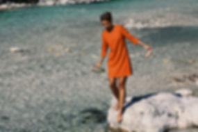 Sandra Fleckenstein im orangenen Kleid an einem Fluss