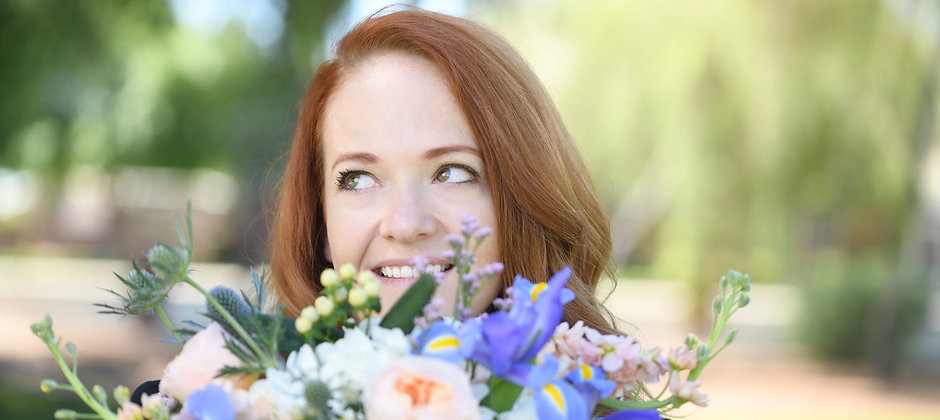 Michelle looking over a beautiful white and blue flowers