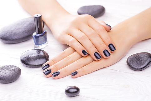 Black nail polish on manicured hands manicure with gel polish