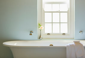 Bath tup below window with towel and bar of soap on edge of tub.