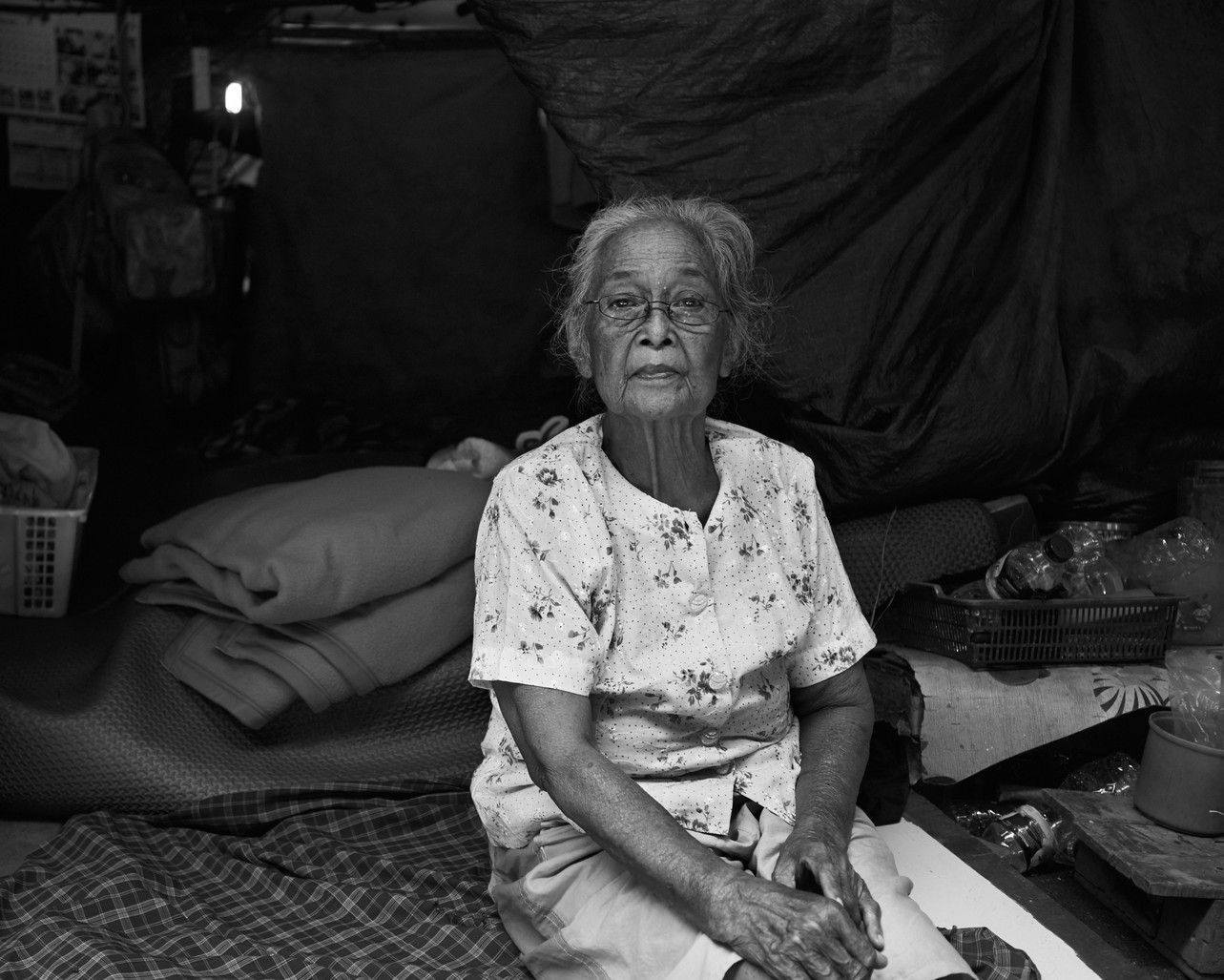 Located at the end of the alleyway, Ibu Nasrih set up a homemade tent where she lives with her mother (in this picture), husband and daughter Asti. Ibu Nasrih's mother is disabled and would sit in this position all day as the constant traffic passes by above her.