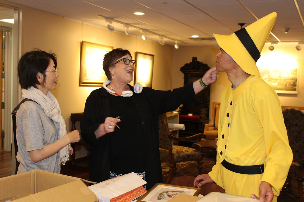 Three people in a group, one dressed in a yellow top and yellow hat.