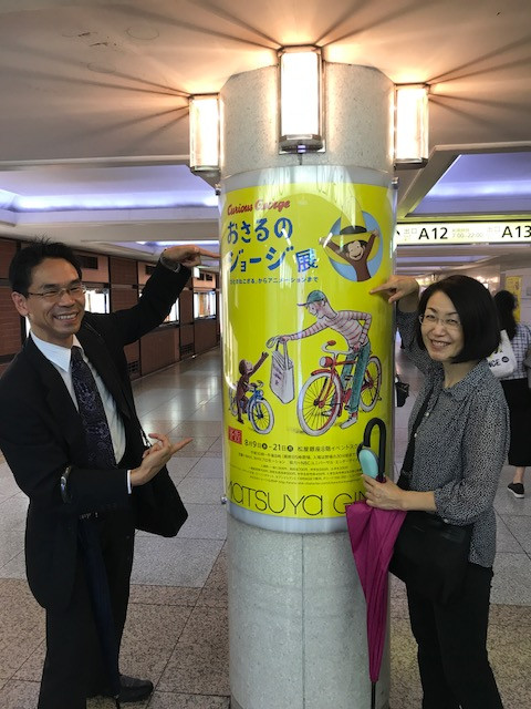 Photograph of a man and woman pointing to a poster on a column.