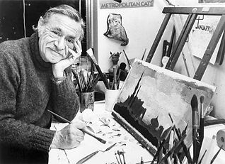 black and white image of Ezra Jack Keats, leaning on his elbow on his drawing table. He is holding a paint brush in his right hand in front of a painting.