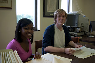 Photo of two students sitting at a table working on papers from the de Grummond Collection