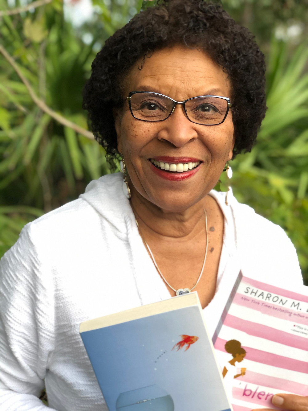 African American woman in a white shirt, holding two books in her hand.