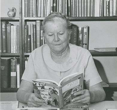 Black and white image of Lena de Grummond sitting a desk, reading a book. Behind the desk are bookshelves with books.