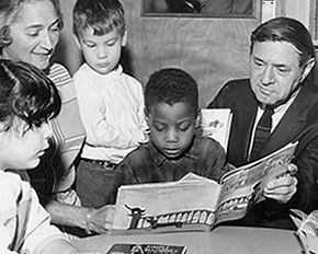Black and white image of four children, one holding a book and Ezra Jack Keats leaning over the child's shoulder.