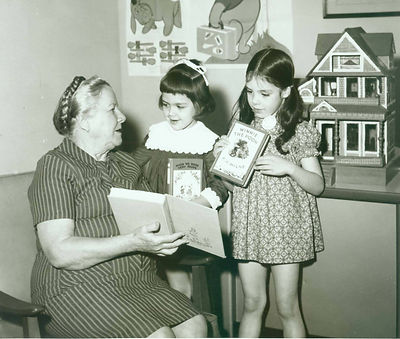 Black and white image of Lena de Grummond sitting in a chair readings a book to two small children. The two children are facing de Grummond, holding books.
