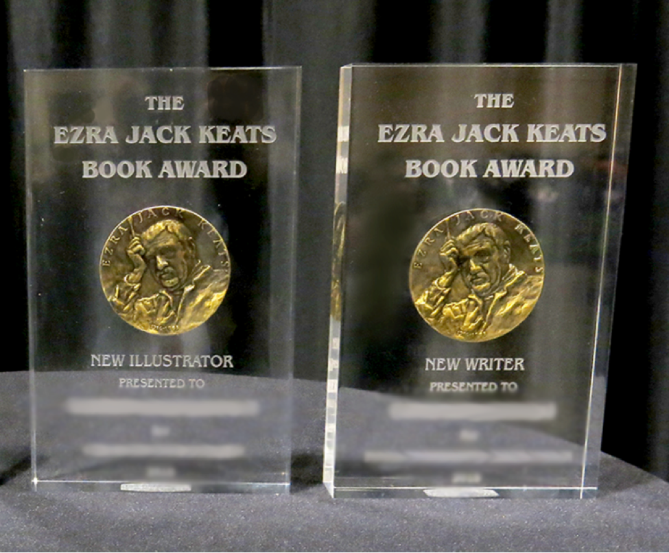Two clear recognition pieces side by side. The item on the left says The Ezra Jack Keats Book Award, New Illustrator, and the item on the right reads The Ezra Jack Keats Book Award New Writer Presented to. In the center of each is a gold medallion with an image of a man.