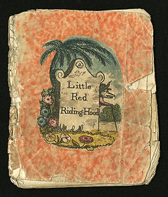 Image is an old story book cover of little red riding hood. The book is red with in image in the middle. The image contains a palm tree over a sign that says Little Red Riding Hood and flowers surround the sign.