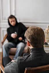 man-in-gray-hoodie-sitting-on-couch-4100