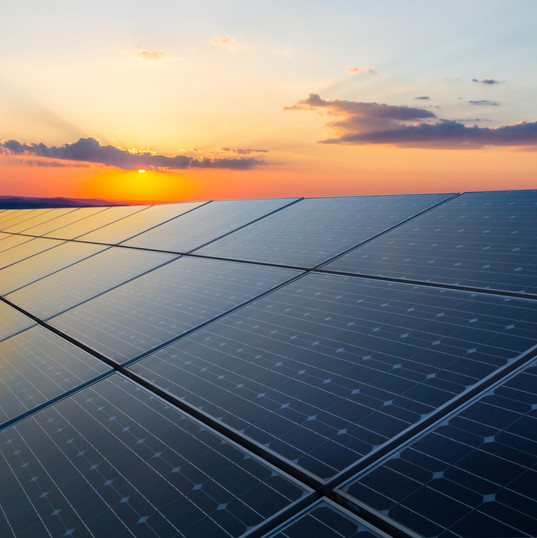 Sunset rays over a photovoltaic power plant.jpg