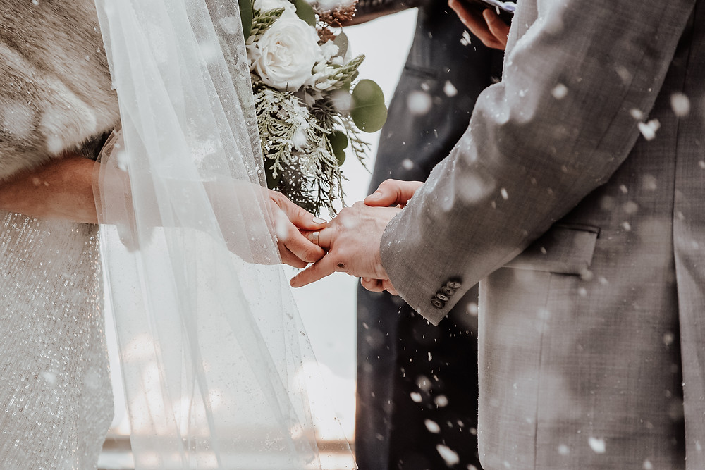 Ring exchange between bride and groom during snowy winter wedding ceremony in Rossland BC