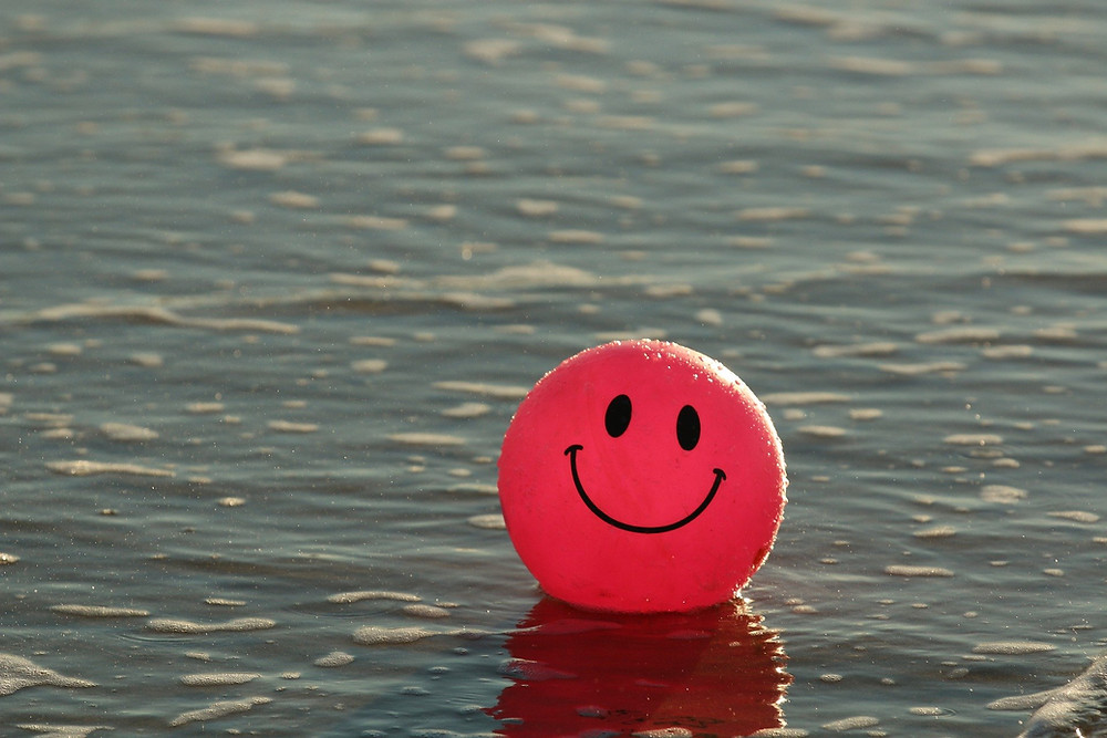 A red bouncy ball with a smiley face floating in the sea.